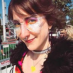 Stephanie Paulantis on a sunny day with brightly colored glitter makeup under clear heart glasses, wearing and a fuzzy black hood.