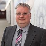 Scott Chandler, smiling, wearing glasses.