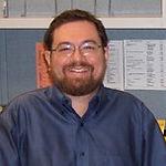 John Lee, smiling, wearing glasses.