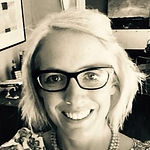 Eliza Bullock, smiling, wearing glasses, black and white.