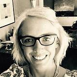 Eliza Bullock, wearing glasses, smiling in black and white.