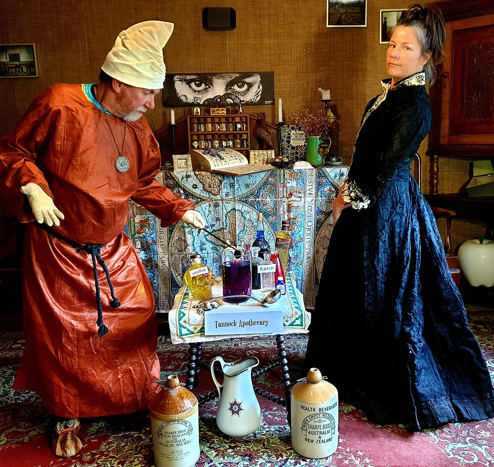 Man & woman posing with potions and vials
