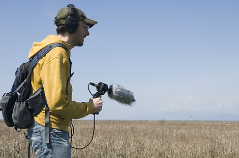 Young man recording nature sounds outsid