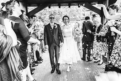 Bride and groom get showered with confetti while holding hand and smiling.
