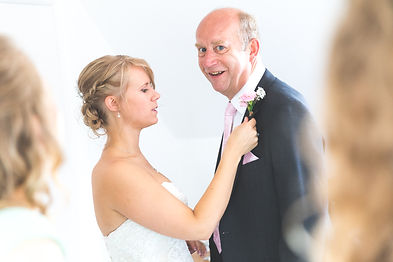 Intimate moment where bride is helping her father with his button hole flowers. Father is smiling at camera