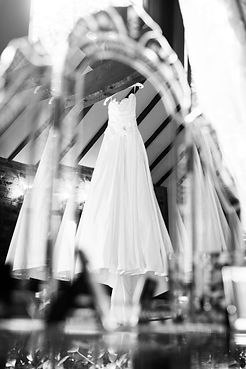 Photo of wedding dress hanging from beams in the mirror