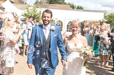 Bride and Groom walk through bubbles as confetti holding hands on sunny day.