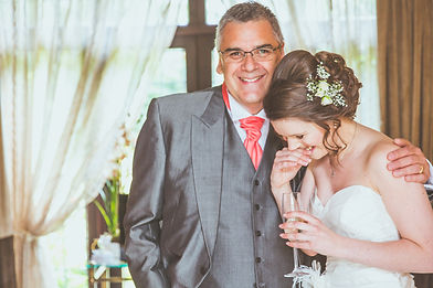 Intimate moment between bride and her father hugging and happy