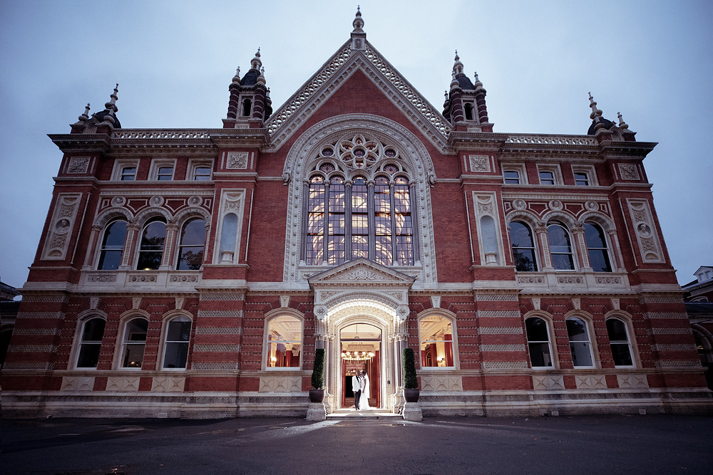 Bride and Groom kiss under the main hall arch at Dulwich College. Photography by Editorial Wedding Photographer Shane Anthony Sinclair Beckenham Wedding Photographer London Wedding Photographer