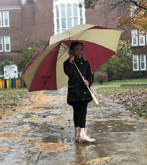Student poses for a picture on a rainy day.