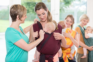Group of women learning how to use baby slings for mother-child bonding.jpg