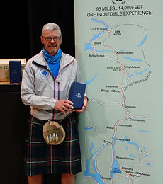 Matt in his kilt, with his finishers goblet & The Ron Hill West Highland Way Race Map