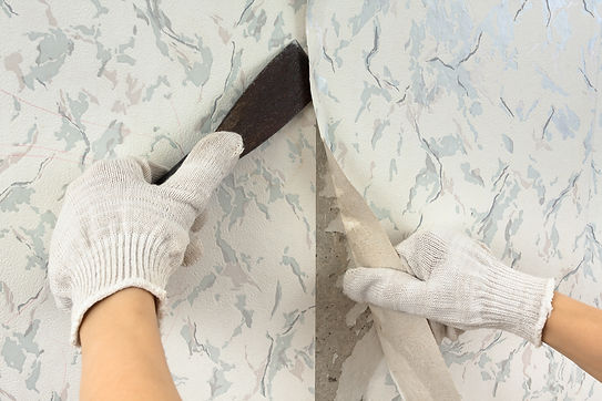 hands in glove removing old wallpaper wi