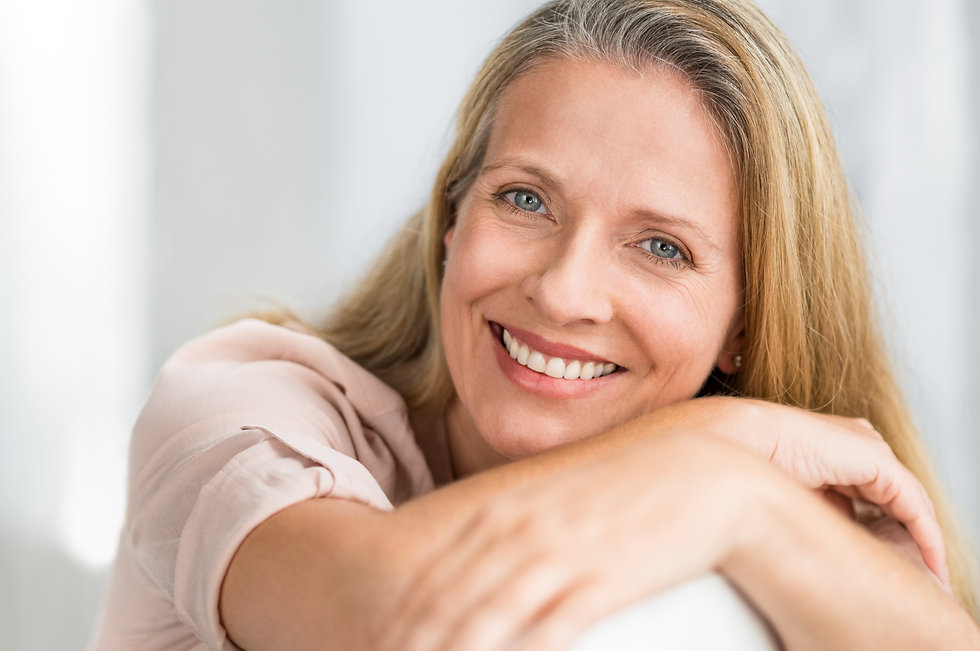 smiling-mature-woman-on-couch-JEHUQVG.jp