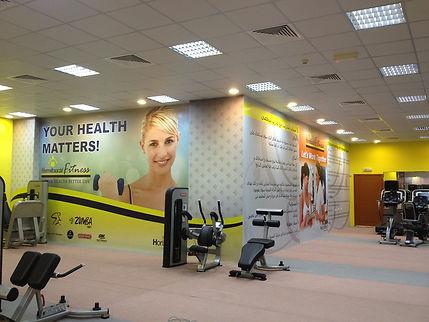 gimnasio con pared grande rotulada con una mujer