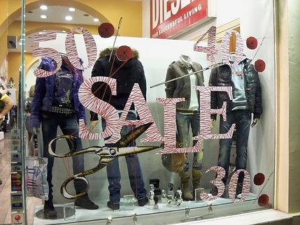 escaparate de tienda de ropa con rótulos de se vende y descuento