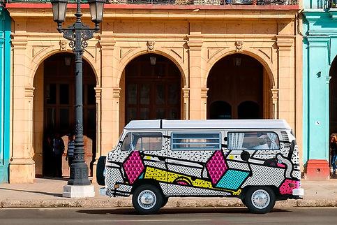 furgoneta rotulada con figuras geométricas delante de fachada artística
