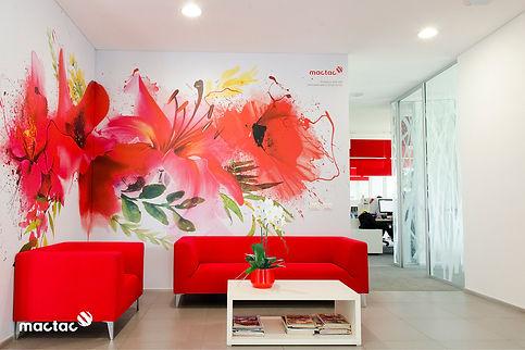 recibidor de oficina con sofá rojo y pared rotulada con flores rojas