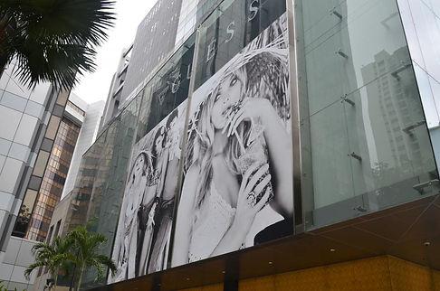 panel publicitario rotulado con mujer y colocado en fachada de edificio