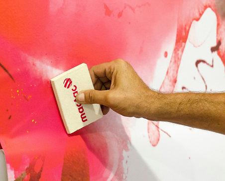 mano de hombre colocando panel de vinilo con espátula de fieltro