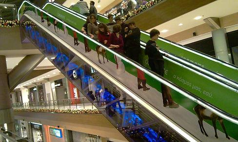 gente en escalera mecánica con lateral rotulado