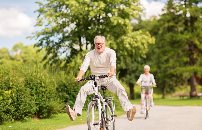 active old age, people and lifestyle concept - happy senior couple riding bicycles at summ