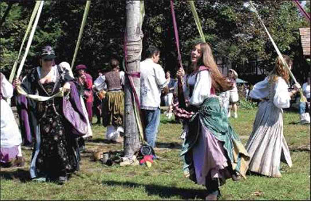 People in costume dancing around a Maypole