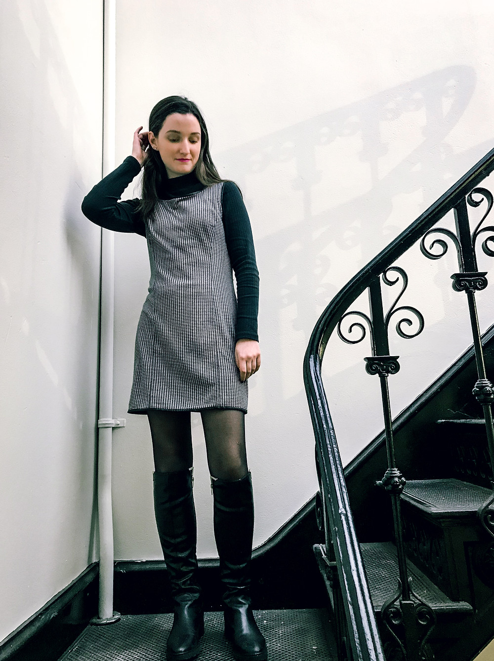 black and white layered dress with turtleneck and high boots