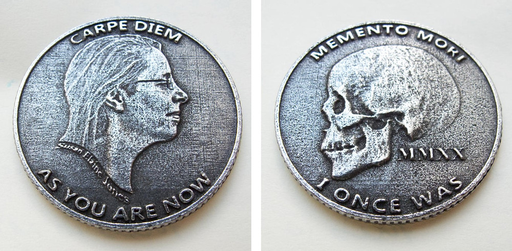 silver coin with a face on one side reading carpe diem and as you are now and on the other side a skull with memento mori and I once was. Dated year MMXX 2020, the year of Covid.