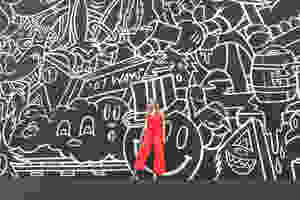 girl in orange outfit against black and white graffiti wall