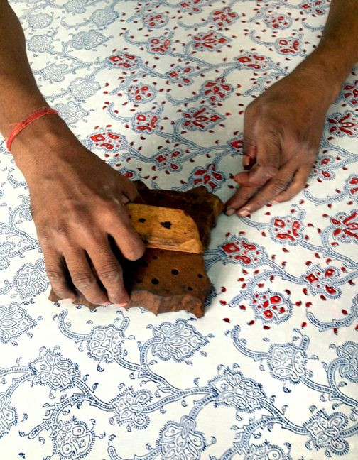 Block printing being completed by hand.