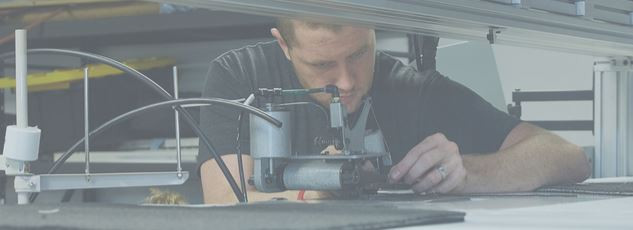 a skilled worker adjusts a piece of SoftWear equipment