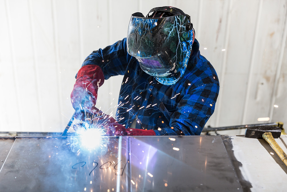 Welding professional modifying a reefer container for storage adaptations. giving great modifications for you cold store