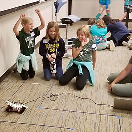 Girl scouts cheer at robot in maze