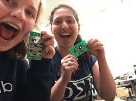 Two women smiling holding circuit boards