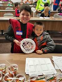 Two little boys showing off thier completed string spider web