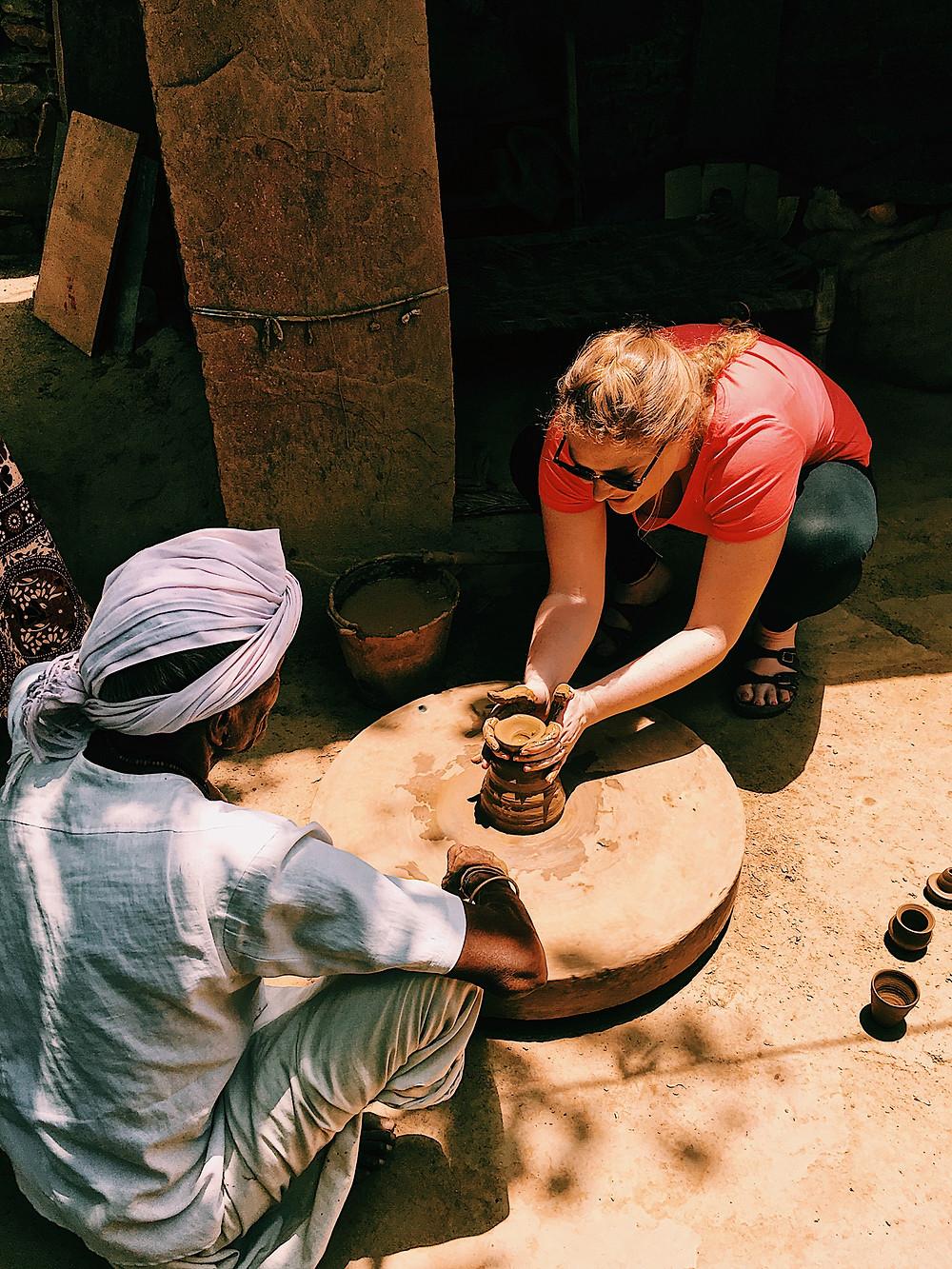 Leah making pottery via a hand spun wheel