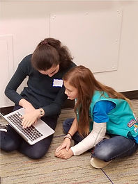 College student and girl scout look at computer