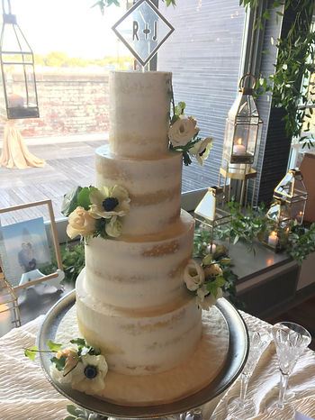 Semi-naked wedding cake with fresh flowe