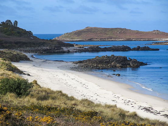 Blue sky and blue sea around a sandy beach with rocky outcrops - this is Great Bay on St Martins, Scilly