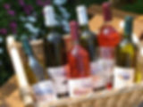 A selection of white, red and rose wine bottles in a wicker display basket with flowers in the background
