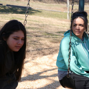 Marili Mejias and Hope Perry on swing set before a take on BUMMER