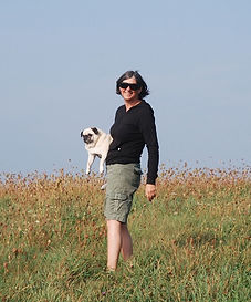Christine on a hill carrying her old pug dog