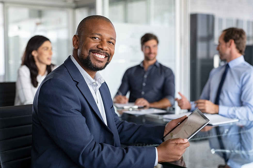 Proud mature black businessman smiling with colleagues sitting in a board room. Portrait o