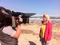 Jo Milne in front of camera, filming on location at Low Newton by the Sea