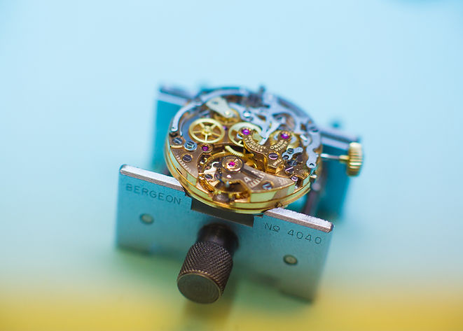 Product photography showing working gears of clock face with gems at the watchmakers shop in asheville, nc