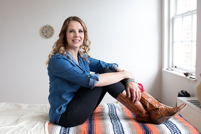 photo of sarah cosgrove owner of grove manor flooring in hendersonville, nc. Sitting in her reike studio on a massage chair, she is wearing cowboy boots, demin shirt and black jeans. She has long blonde curly hair.