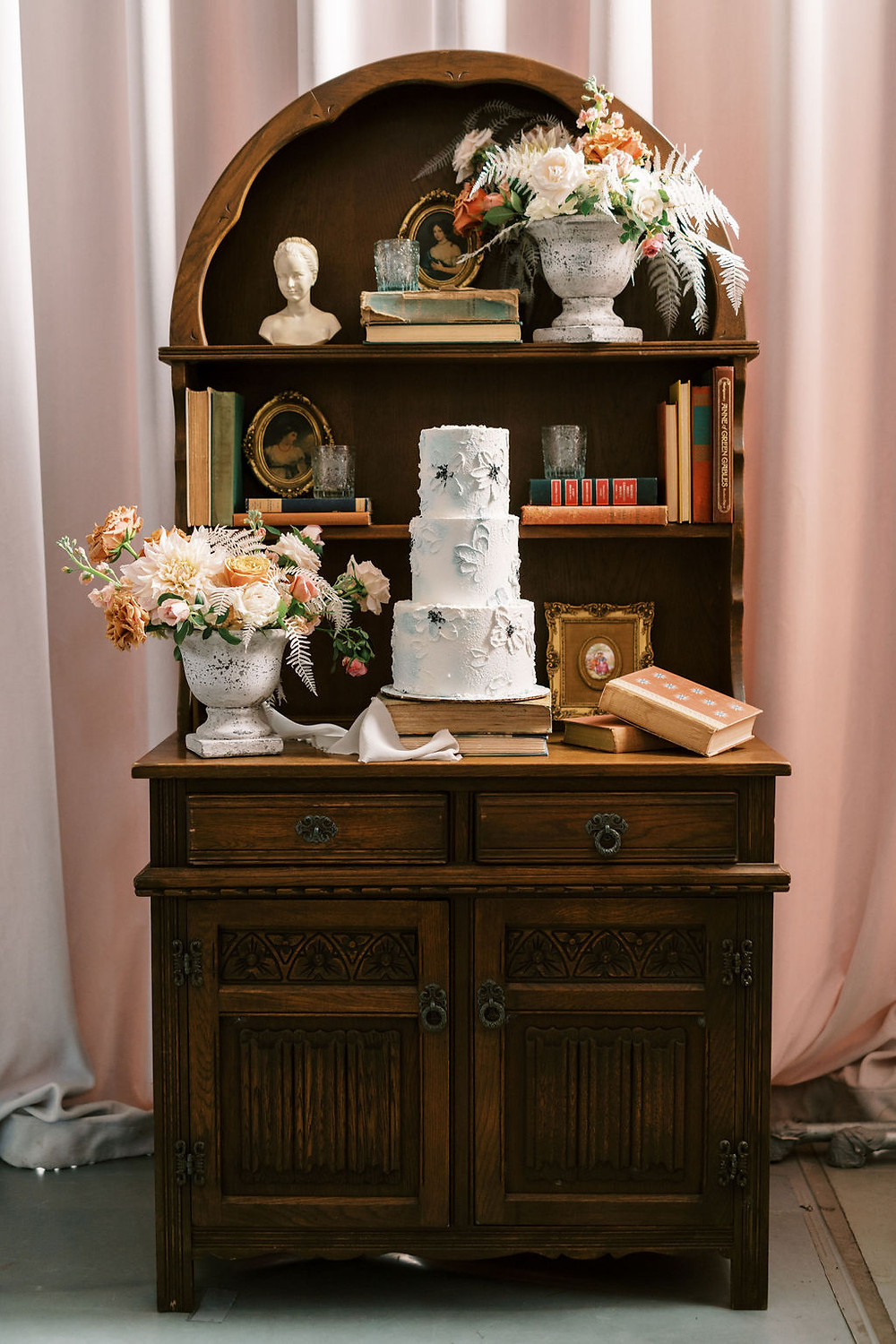 Bookcase with Wedding Cake, Vintage Books, and Antique Decor for Bridgerton Inspired Wedding at the Marigny Opera House in New Orleans with Lounge Spaces and Vintage Furniture by Lovegood Rentals