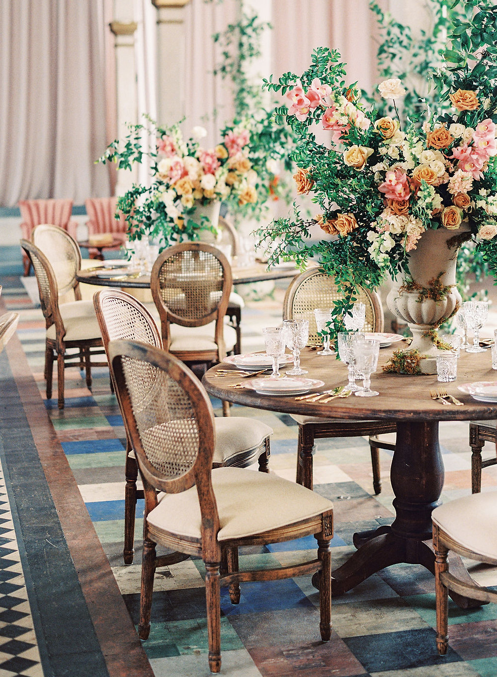 Seated Dinner for Bridgerton Inspired Wedding at the Marigny Opera House in New Orleans with Decor, Lounge Spaces, and Vintage Furniture by Lovegood Rentals Featuring Caned Louis Chairs, Round Mahogany Tables, Gold Flatware and Overgrown Florals