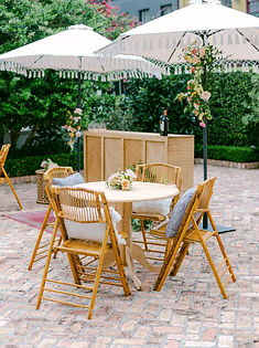 "Outdoor Courtyard with Light Colored Wooden Bar, Bamboo Folding Chairs, 36"" Round Light Colored Wood Tables, Pillows in All the Chairs, Small Arrangements on all the tables, Dark Rose Pink Rug on Ground with Tassel Umbrellas decorated with flowers"